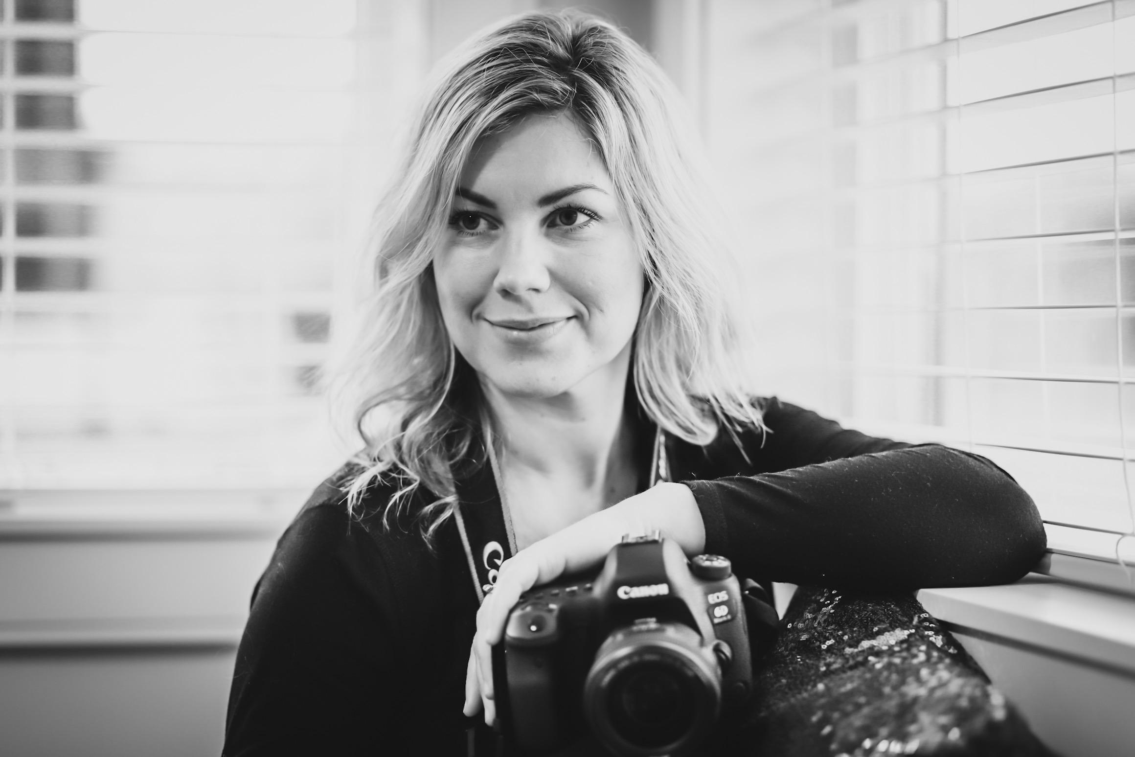 Black and white portrait of a Shannon Kay, a blonde woman photographer holding a Canon camera.